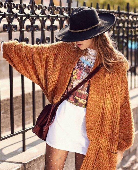 Oversized cardigan; mujer posando en barandales de casa, con sombrero, playera de The Beatles, Sgt. Pepper's Lonely Hearts Club Band, con suéter holgado tejido color anaranjado