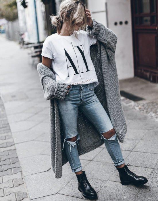 Oversized cardigan; mujer rubia con coleta despeinada, con playera de Armani, con pantalones rasgados, botas militares y suéter holgado tejido color gris, en la calle
