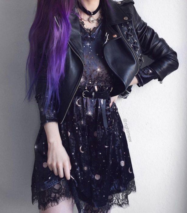 Ropa de constelaciones; mujer de cabello morado y largo, con vestido de universo con lunas y estrellas y tela de encaje, con chamarra de cuero
