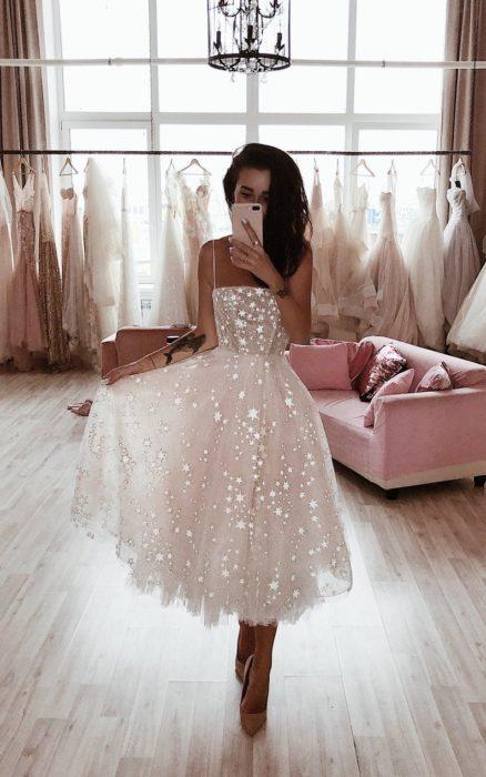 Ropa de constelaciones; mujer tomándose selfie frente al espejo con vestido blanco de tirantes y tela de gasa con estrellas