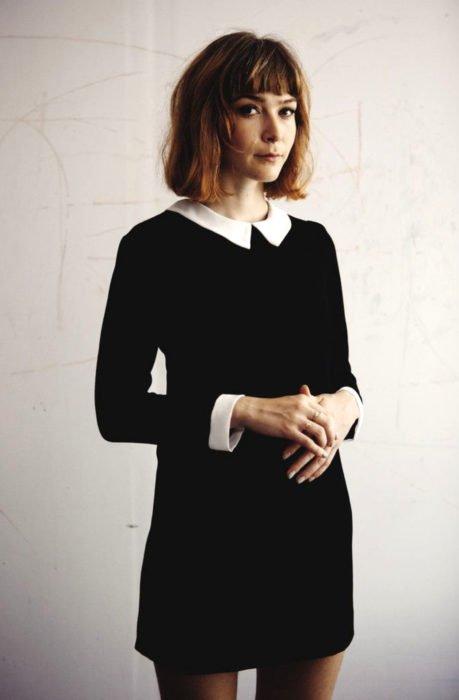 Chica de cabello castaño claro y corto con vestido de Merlina Adams color negro con cuello blanco