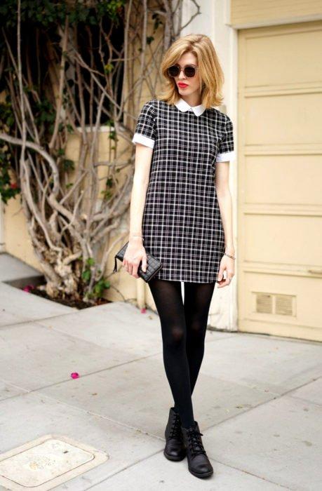 Chica de cabello rubio corto vestida de Merlina Adams; vestido de cuadros negros y blancos, con medias y botines
