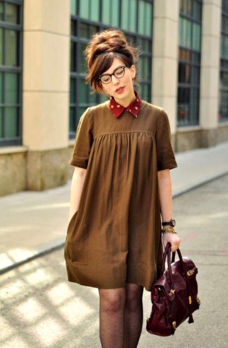 Chica con lentes vintage vestida de Merlina Adams; con vestido café retro con cuello rojo de lunares blancos, peinado de chongo alto