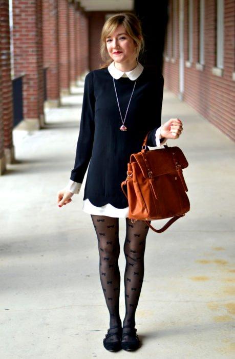 Chica vestida de Merlina Adams; vestido negro con cuello blanco, bolsa de mano café, medias de moños y flats