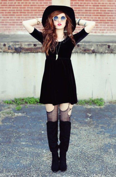 Chica vestida de Merlina Adams; con sombrero de ala gruesa, vestido de terciopelo negro, medias rotas y botas altas