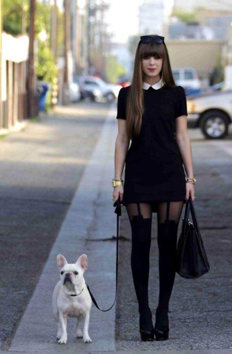 Perro bulldog francés y chica vestida de Merlina Adams; vestido negro con cuello blanco, medias y bolsa de mano