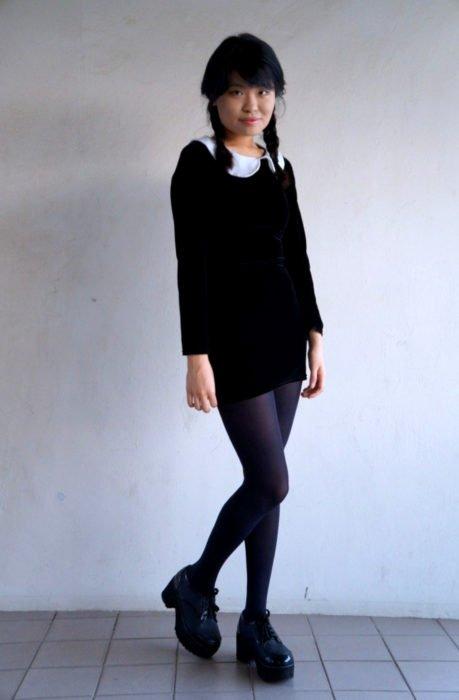 Chica asiática vestida como Merlina Adams; vestido negro, corto, con cuello blanco, zapatos de plataforma y peinado de trenzas