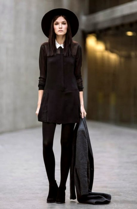 Chica de cabello lacio y mediano, con sombrero, vestido, medias y botines negros, con abrigo fris