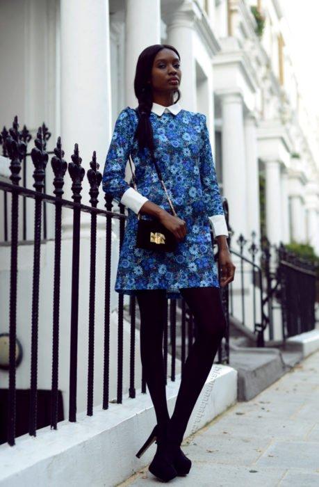 Chica morena vestida de Merlina Adams; vestido azul, de flores, con cuello blanco, medias negras y botas de tacón de aguja
