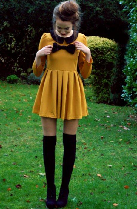 Chica vestida de Merlina Adams; vestido amarillo mostaza con moño negro, medias, botines, con peinado de chongo alto