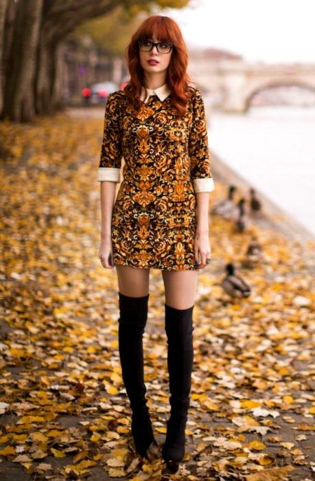 Chica pelirroja con lentes vestida de Merlina Adams; vestido de ornamentos color amarillo con negro, con botas negras altas
