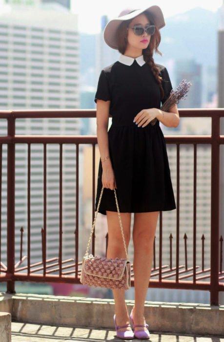 Chica vestida de Merlina Adams; vestido negro con cuello blanco, zapatos morados, sombrero lila, con lavanda en la mano y con lentes de sol