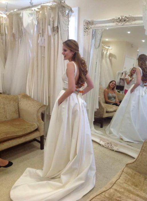 una mujer probándose un vestido de novia frente a un espejo en el que se reflejan otras personas que la observan