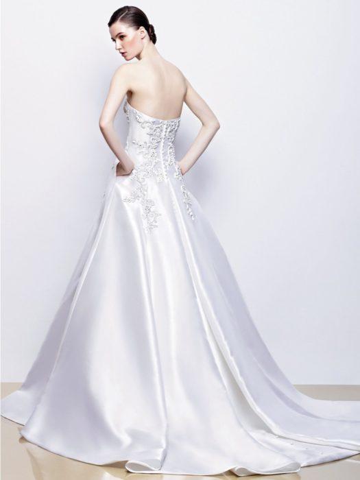 una novia posa de espaldas para que se observe la parte trasera de su vestido, recarga sus manos sin meterlas completamente en los bolsillos del vestido