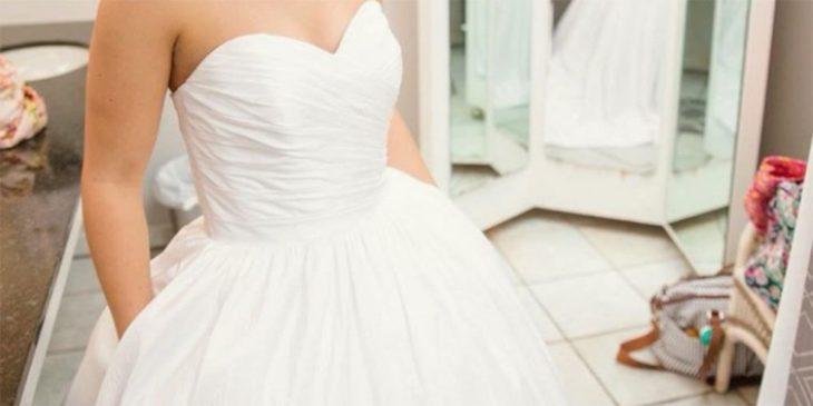 el torso de una mujer con un vestido de novia vaporoso con las manos dentro de los bolsillos laterales del vestido