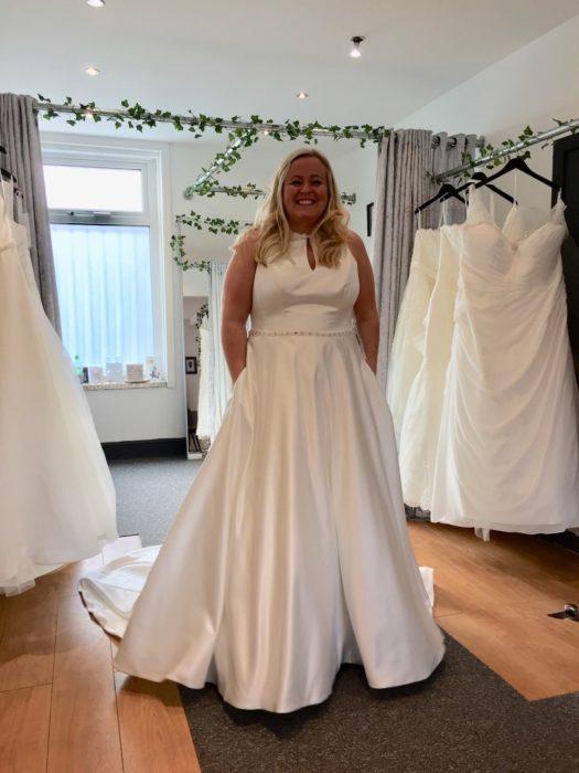 Una mujer con un vestido de novia en una tienda de vestidos, tiene las manos dentro de las bolsas