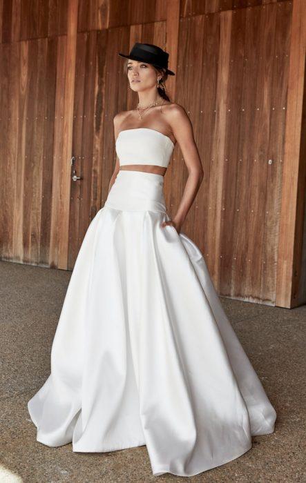 una mujer posa con un vestido de novia de dos piezas, en la falda amplia lleva las manos dentro de su bolsillos