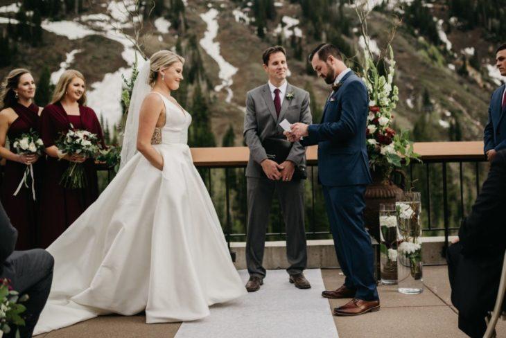 una ceremonia matrimonial, el novio lee un papel mientras que la novia lo mira con las manos dentro de las bolsas de su vestido