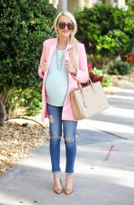 Chica embarazada usando jeans, sueter de color verde y abrigo de color rosa coral