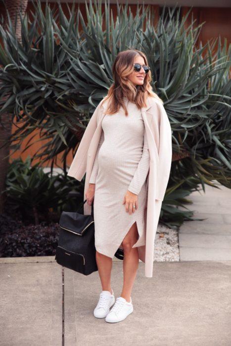 Chica embarazada posando para una foto mientras usa un vestido de color rosa y un abrigo del mismo color