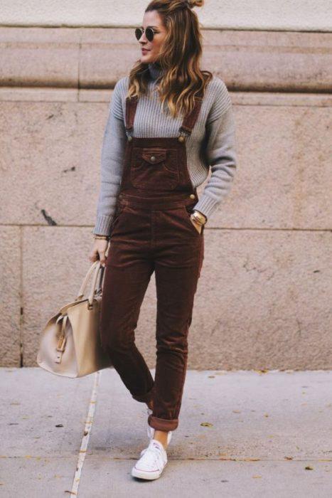 Chica usando un overol de pana de color vino con un suéter de color gris