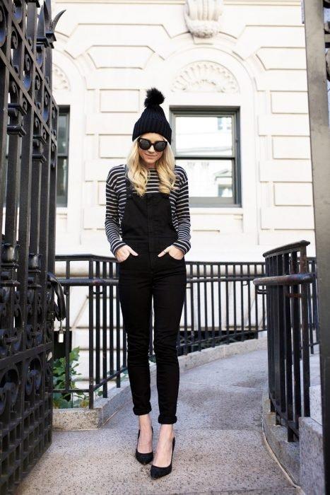 Chica usando un overol negro, camisa de líneas blancas y negras y gorro de lana negro