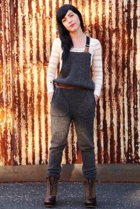 Chica usando un overol de lana de color gris y botas militares mientras está posando para una foto