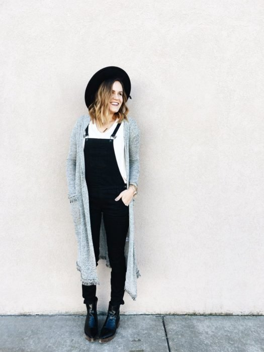 Chica usando un overol de color negro con un ensamble de color gris