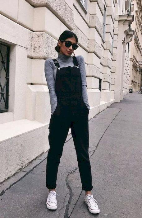 Chica usando un overol de color negro con una blusa de color gris