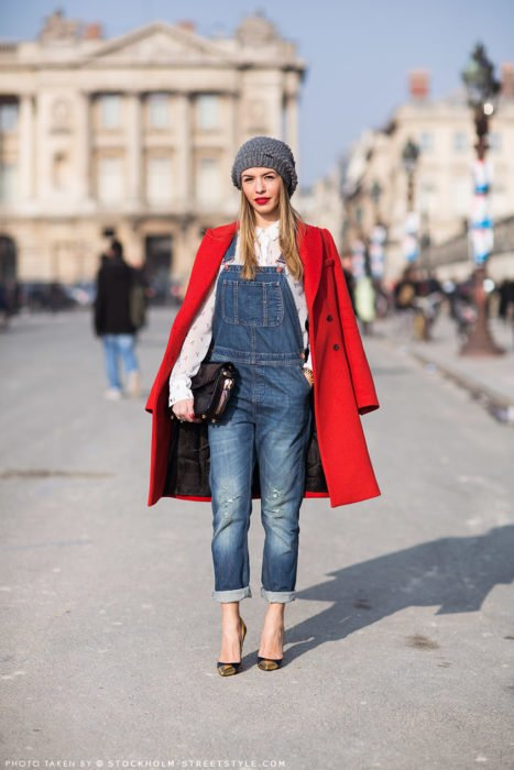 Chica usando un overol con un abrigo de color rojo y un gorro gris