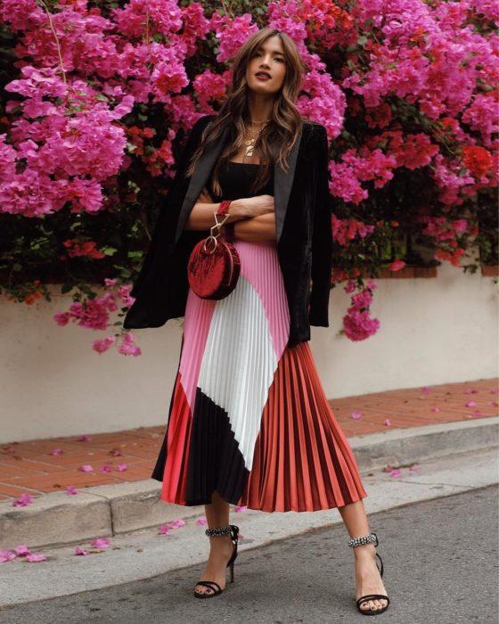 chica con chamarra negra y falda plisada de colores