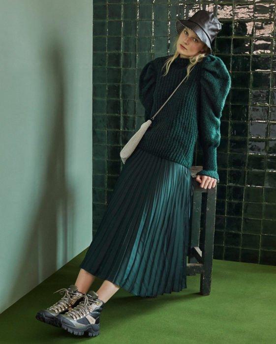 chica con falda plisada metálica verde y suéter de mangas amplias verde