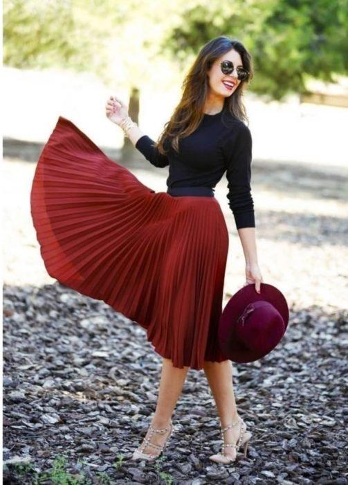 chica con suéter negro y falda plisada rojo oscuro