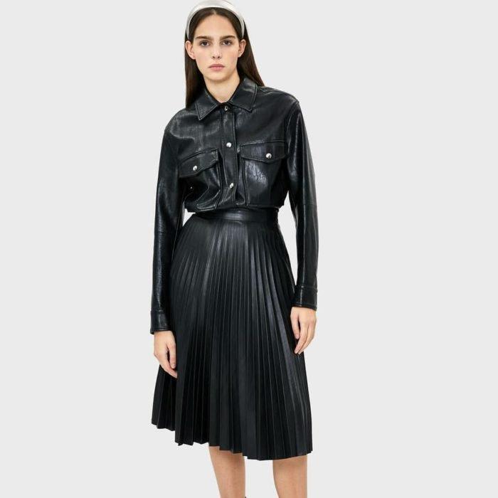 chica con falda plisada negra y blusa de piel sintética negra