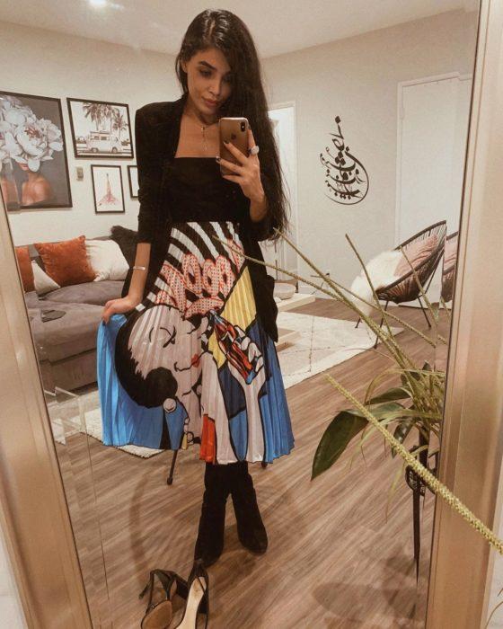 chica con blusa negra y falda plisada estampada con dibujos animados