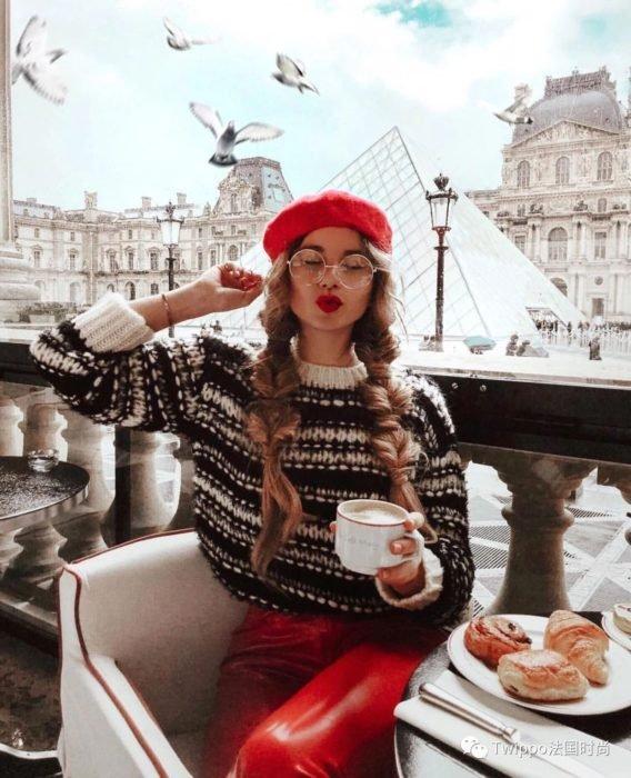 Chica sentada en un café de París usando un feo suéter navideño mientras toma un café