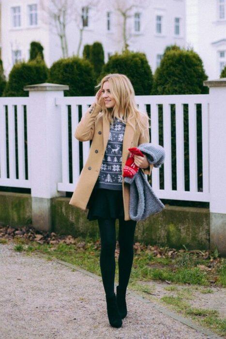 Chica usando un ugly sweter de color gris con una chaqueta café, medias, botas y falda negras
