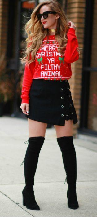 Chica usando un feo sueter navideño con botas largas y falda de color negro