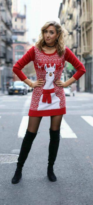 Chica usando un ugly sweter con unas botas largas de color negro y medias