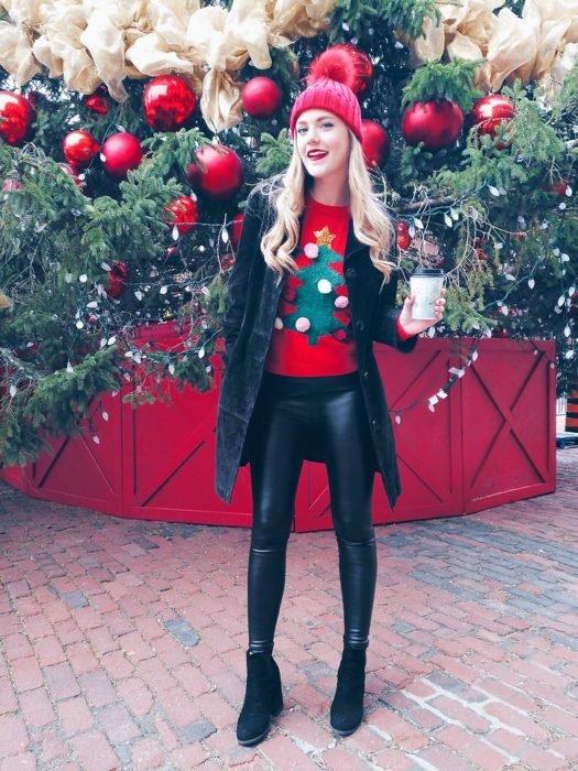 Chica usando un feo sueter navideño con una chaqueta de color negro y leggins de cuero color negros