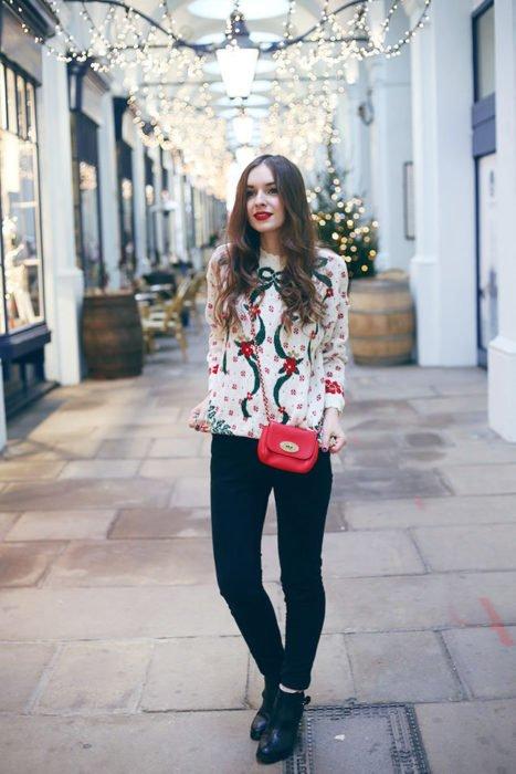 Chica usando un feo suéter navideño con unos jeans y botines