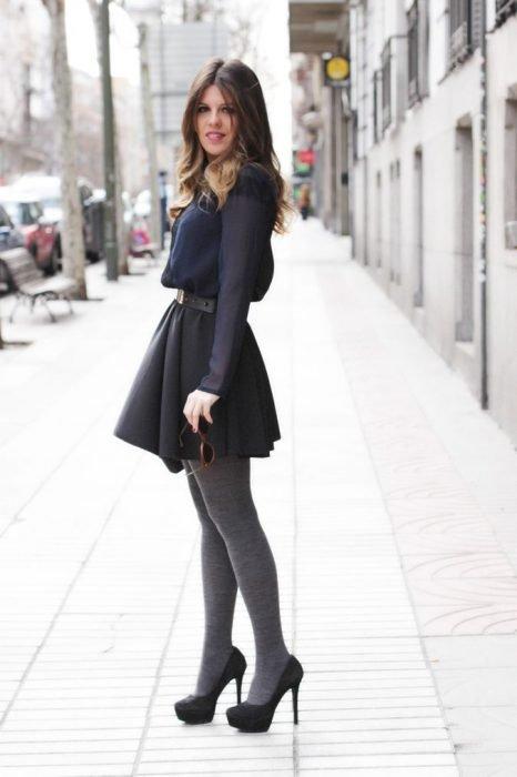 Chica usando un vestido corto de color gris con medias y tacones