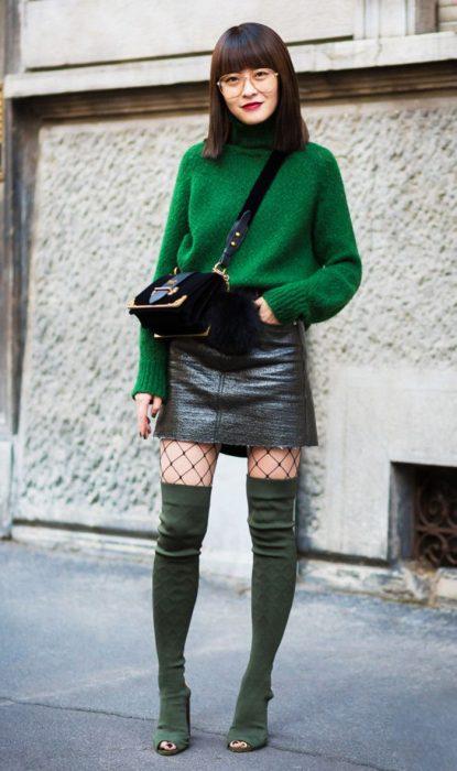 Chica usando un suéter, botas verdes, medias de red y falda de cuero