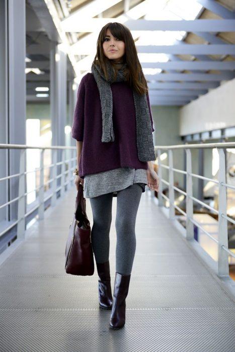 Chica caminando mientras usa un abrigo de color guinda, bufanda y medias de lana en color gris con botines