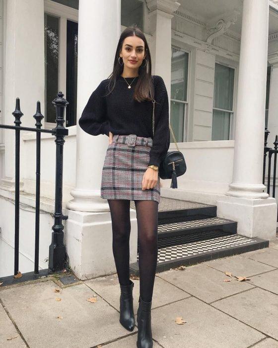 Chica afuera de su casa usando medias negras, suéter de color negro y falda estilo escocesa