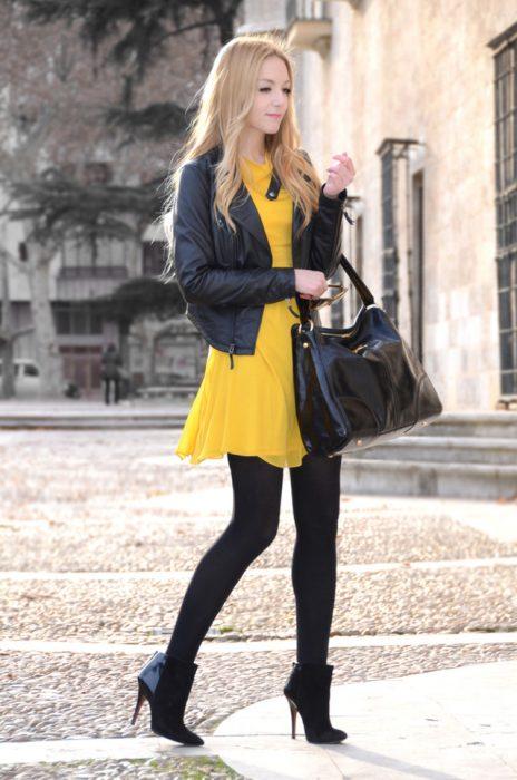 Chica usando un vestido de color amarillo con medias de color negro y botines
