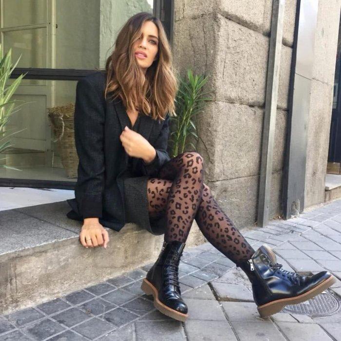 Chica usando un outfit de color negro con medias de estampado de leopardo y botas dr marteen