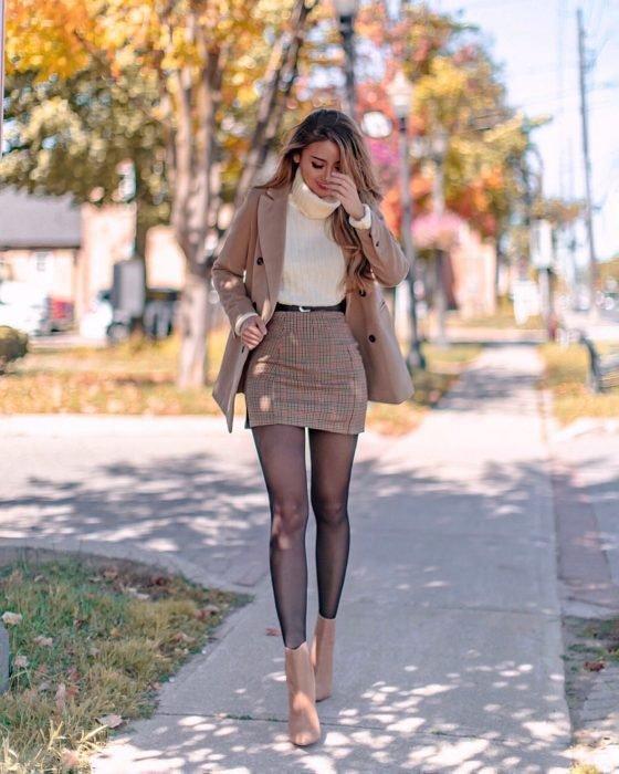 Chica caminando por la calle mientras está usando un outfit de color café con medias negras