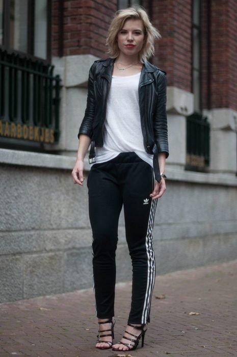 Chica usando un conjunto de pants de color negro con chaqueta de cuero y sandalias de color negro