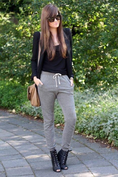 Chica usando unos pants de color gris con una blusa de color negro y zapatos de cintas